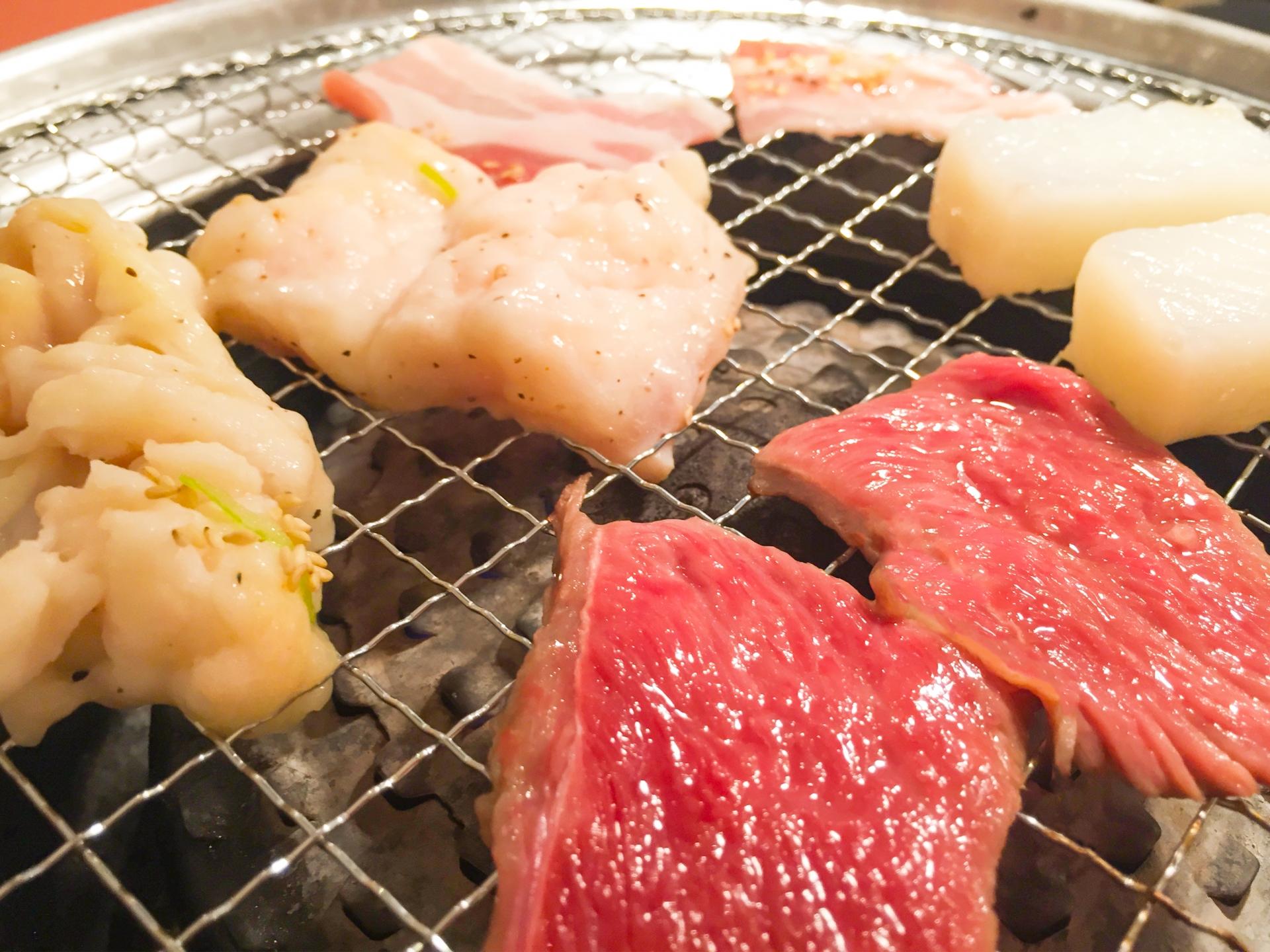 網の上で焼かれている様々な種類の肉とイカ