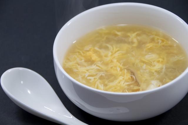 白い器に入った卵スープとれんげ