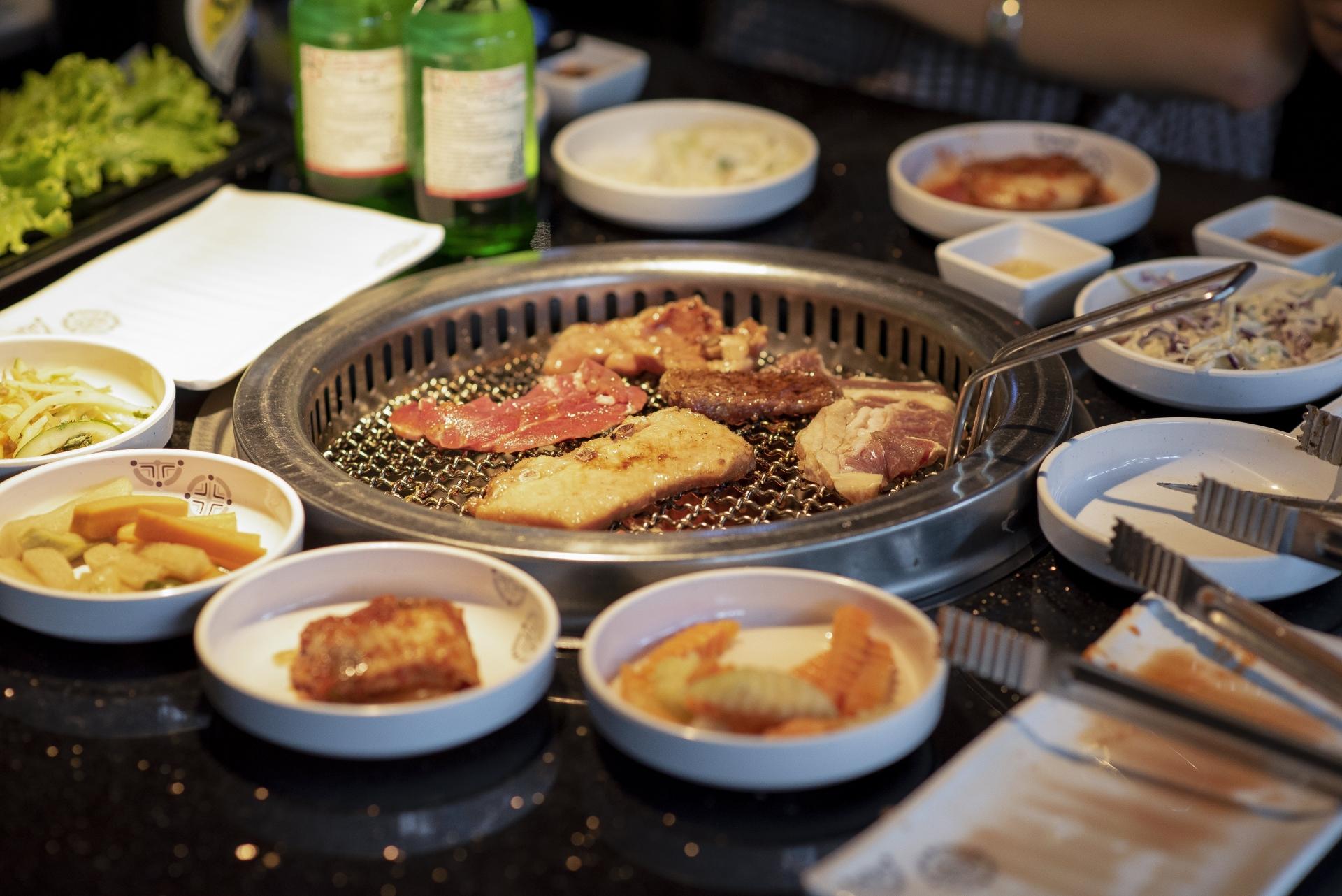 七輪焼肉とその周りを囲むキムチやサラダなどの小皿